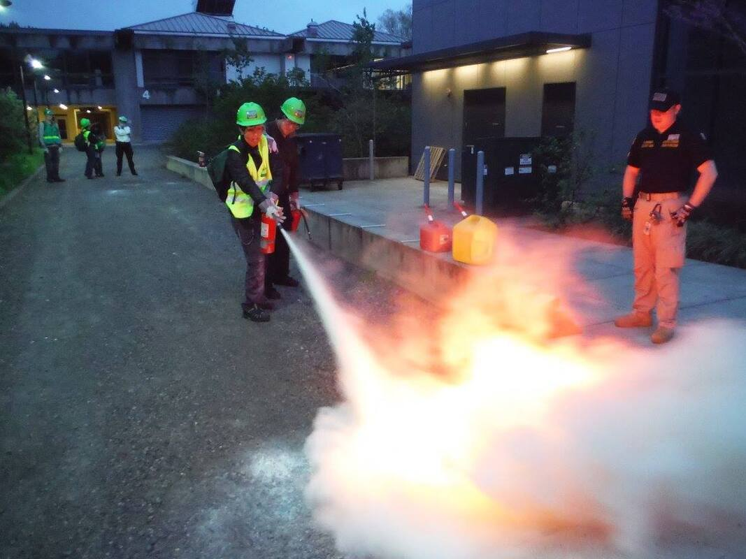 A fire extinguisher training exercises being conducted by an instructor from Training Solutions International.