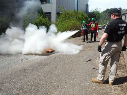 Training Solutions International instructors look on as CERT volunteers practice putting out fires using extinguishers during an exercise put on by TSI for a Basic CERT training class at Lane Community College in Eugene, Oregon.